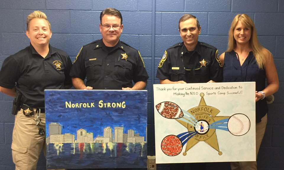 Community Affairs presents artwork from campers to Sheriff Baron and Lt. Col. OToole